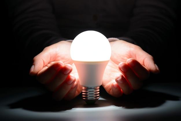 Mani femminili che tengono una lampadina a led incandescente nel buio