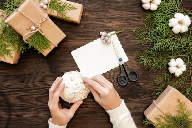 Mani femminili che tengono una palla di natale. realizzazione di giocattoli natalizi fatti a mano