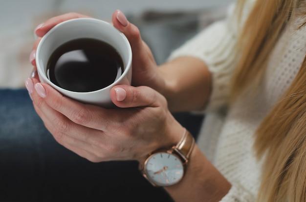 Mani femminili che tengono una tazza bianca con bevanda. concetto di stile di vita. vista dall'alto. avvicinamento
