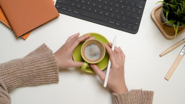 Mani femminili che tengono una tazza di caffè su una scrivania