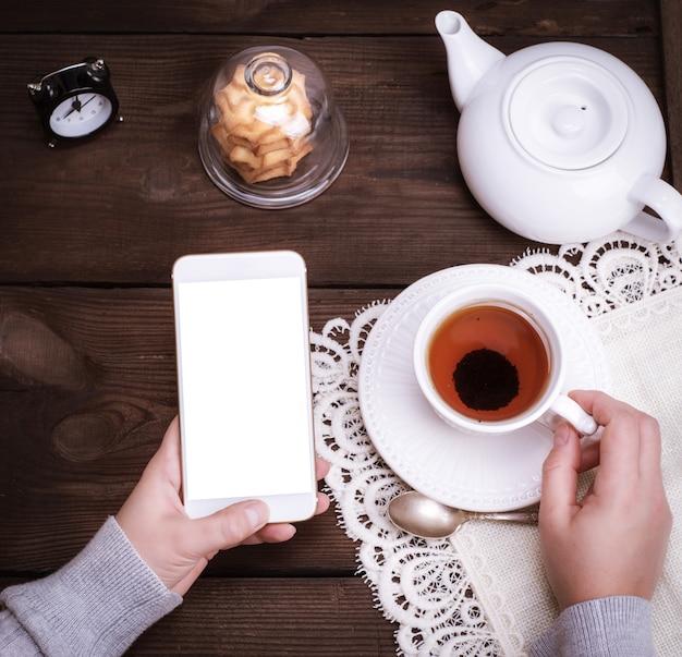 Mani femminili che tengono uno smartphone bianco