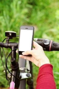Mani femminili che tengono uno smartphone mentre sedendosi su un mountain bike su un sentiero forestale. navigazione concettuale, sport attivi estivi, tecnologia.