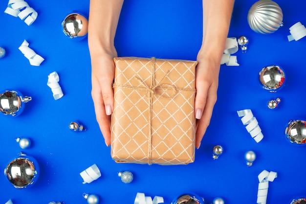 Mani femminili con confezione regalo su un blu