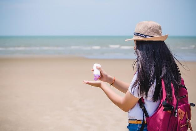 Mani femminili con crema di protezione solare in spiaggia. concep di cura della pelle
