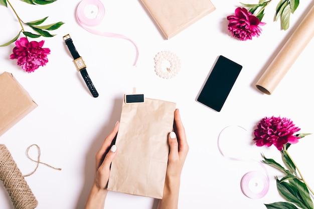 Mani femminili con i regali del pacchetto del manicure su una tavola bianca