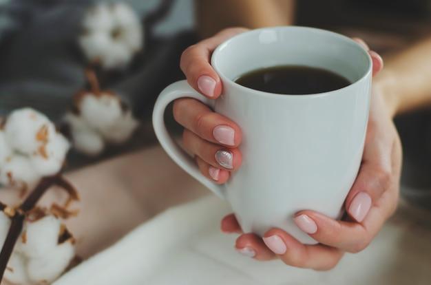 Mani femminili con il manicure colorato pastello che tiene una tazza bianca con la bevanda su fondo luminoso