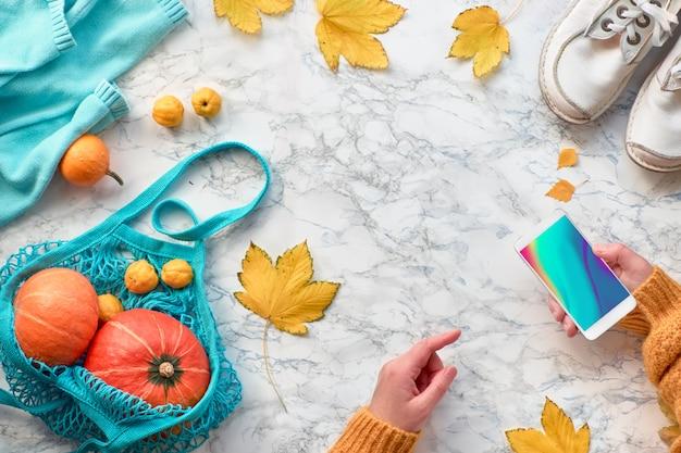Mani femminili con il telefono cellulare, zucche nel sacchetto di stringa, vestiti e foglie gialle