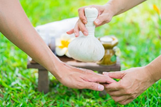 Mani femminili con il vassoio di prodotti della stazione termale sopra canne verdi sul fiume