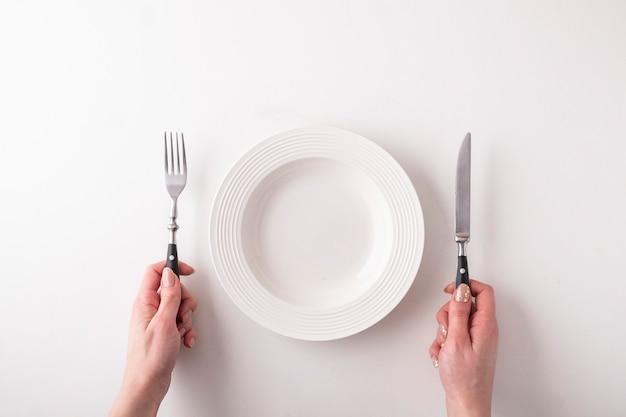 Mani femminili con la forchetta, il coltello e il piatto vuoto su bianco