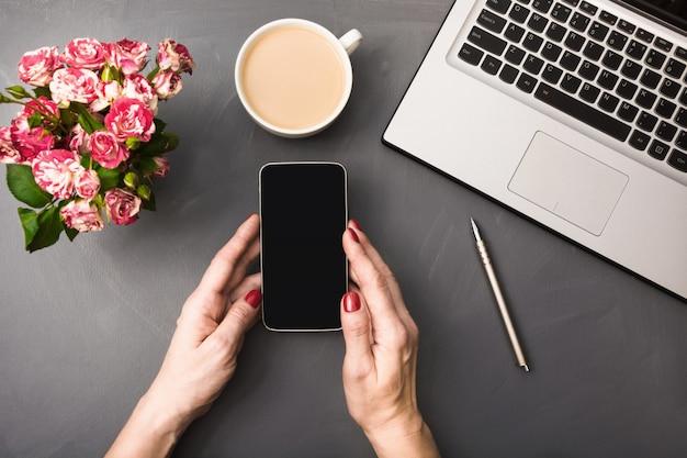 Mani femminili con smartphone, fiori, tazza di caffè e laptop su grigio