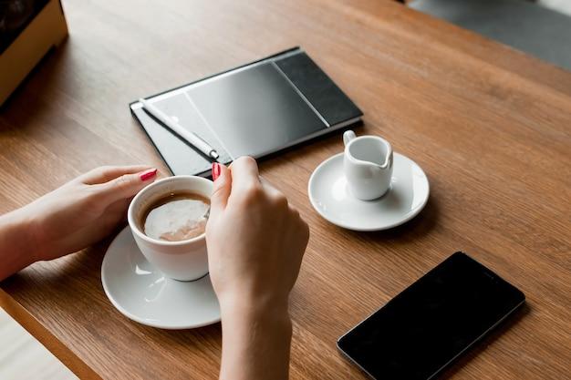 Mani femminili con un telefono nero, una tazza di caffè, tavolo, taccuino