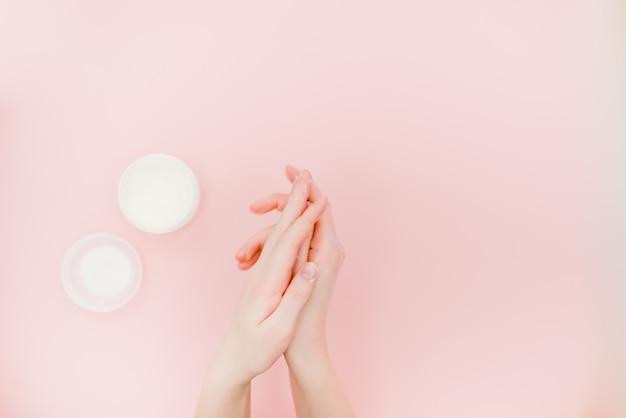 Mani femminili con una scatola di crema per le mani. concetto di cura della pelle della mano.