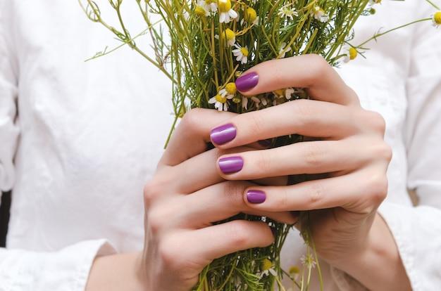 Mani femminili con unghia viola.