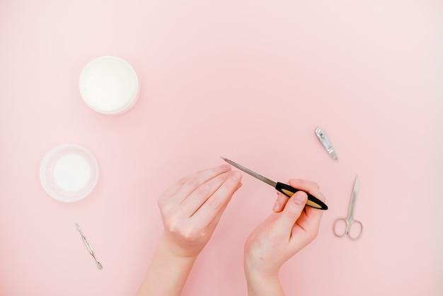 Mani femminili con vaso bianco crema e kit manicure, forbici, lucidante.