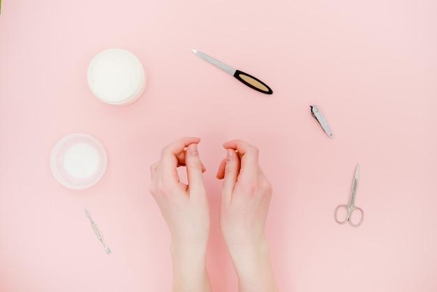 Mani femminili con vaso bianco crema e kit manicure, scissor, lucidante. concetto di cura della pelle.