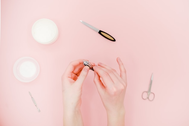 Mani femminili con vaso bianco crema, kit manicure, forbici, lucidatore