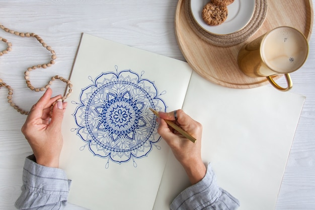 Mani femminili da vicino disegnare mandala floreale rotondo decorativo. hobby e relax domestico. una tazza di caffè e biscotti su un vassoio di legno. sfondo bianco.