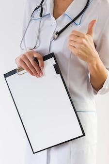Mani femminili del medico che mostrano segno giusto
