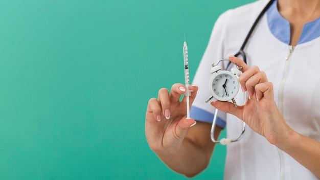 Mani femminili del medico che tengono una siringa e un orologio