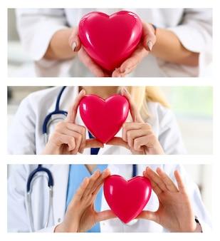 Mani femminili del medico della medicina che tengono cuore rosso