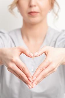 Mani femminili di medico che fa a forma di cuore