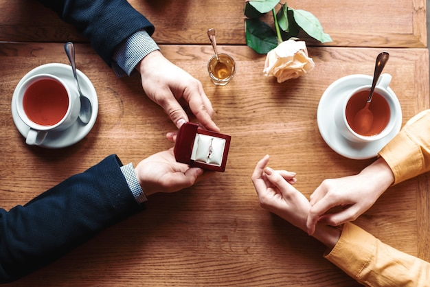Mani femminili e maschili con vista dall'alto di anello nuziale, tavolo in legno, rosa e tazze