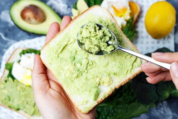 Mani femminili facendo sandwich avocado, vista dall'alto