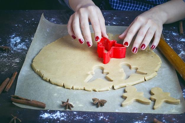 Mani femminili in farina che produce il biscotto di natale sotto forma di uomo di pan di zenzero da pasta in cucina