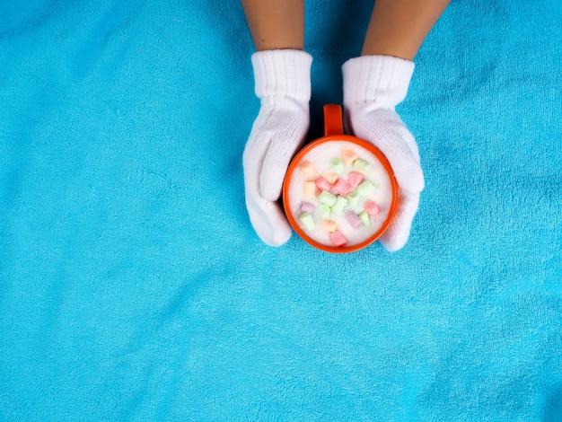 Mani femminili in guanti che tengono la cioccolata calda in una tazza con marshmallow.