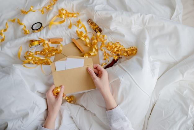 Mani femminili in possesso di carta regalo, busta e confezione regalo sopra la coperta del letto. concetto di natale e capodanno. vista orizzontale superiore