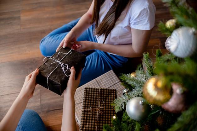 Mani femminili in possesso di regalo. regalo avvolto con carta artigianale.