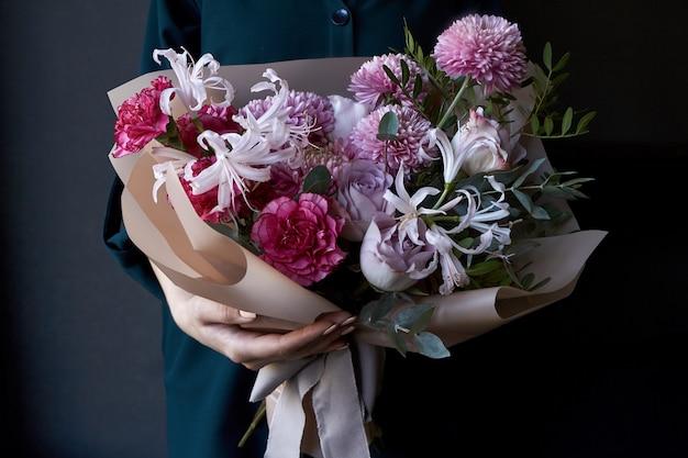 Mani femminili in possesso di un bouquet decorato in stile vintage su uno sfondo scuro