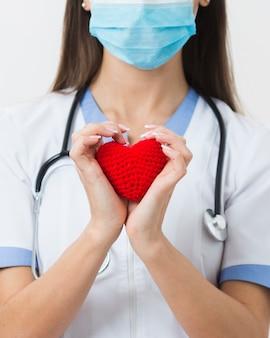 Mani femminili in possesso di un cuore di peluche