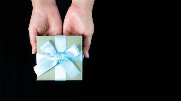 Mani femminili in possesso di un piccolo regalo avvolto con nastro blu