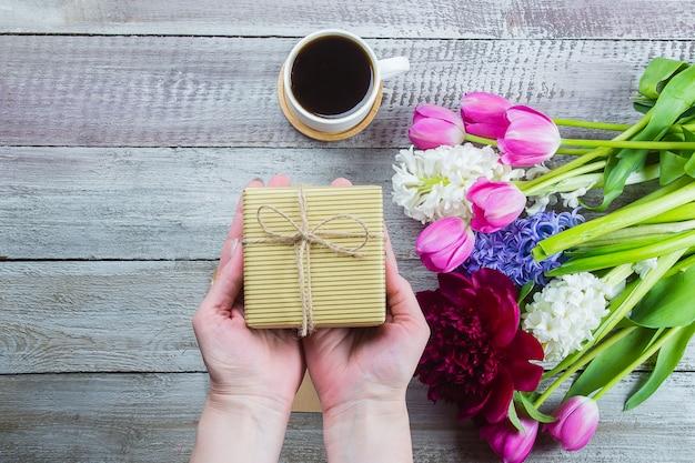 Mani femminili in possesso di un regalo o scatola regalo, tulipani fiori, peonia, giacinto e tazza di caffè nero