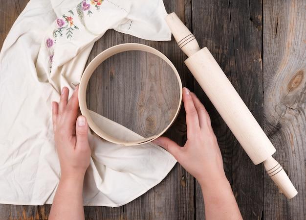 Mani femminili in possesso di un setaccio di legno rotondo per farina, accanto a un mattarello di legno