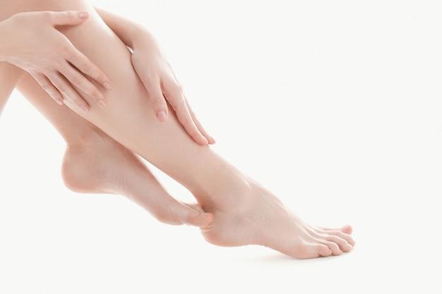 Mani femminili sopra le gambe, concetto di cura del corpo della pelle
