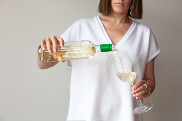 Mani femminili versano vino bianco dalla bottiglia al bicchiere