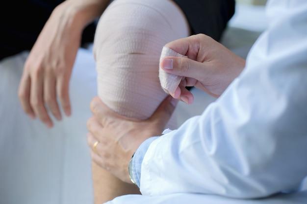Mani fisiche avvolgere il ginocchio al paziente.
