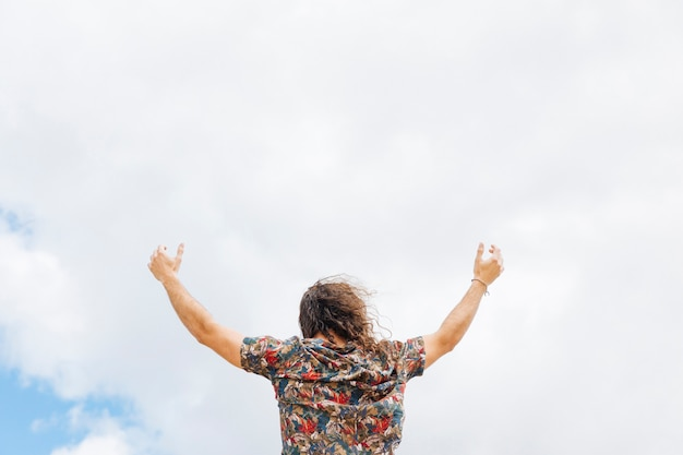 Mani in aumento maschii anonime al cielo nuvoloso