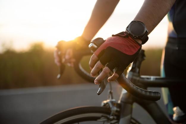 Mani in guanti che tengono il manubrio della bicicletta stradale