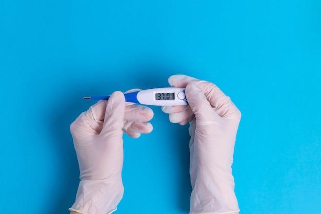 Mani in guanti chirurgici di gomma con un termometro con temperatura corporea normale 37,0 febbre da malattia