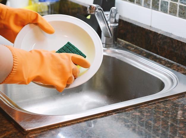 Mani in guanti di gomma lavare i piatti con spon