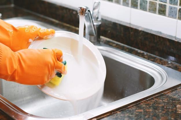 Mani in guanti di gomma lavare i piatti con un cucchiaio