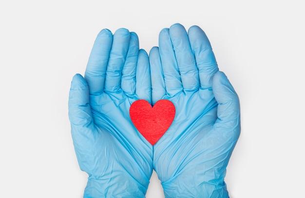 Mani in guanti medici che tengono un modello rosso di forma del cuore su fondo bianco. cardiologia. donazione di organi o concetto di cuore sano