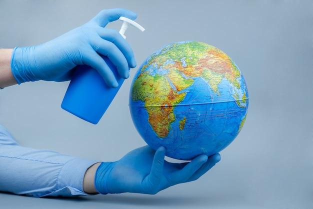 Mani in guanti medici con un globo e un disinfettante. concetto di attacco del mondo coronavirus / corona. concetto di lotta contro il virus.