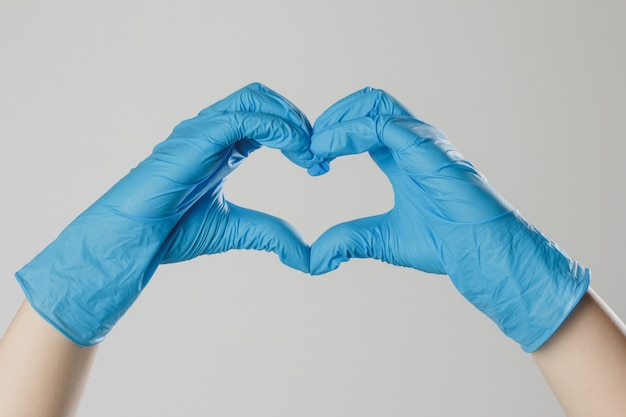 Mani in guanti medici in lattice. le mani formano una forma di cuore. il gesto simboleggia la dichiarazione d'amore.