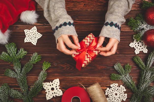 Mani in maglione che tiene un regalo sulla tavola di legno con le decorazioni di natale