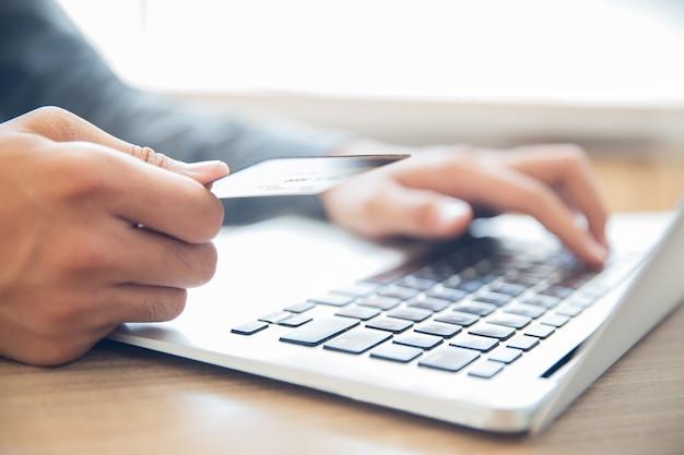 Mani in possesso di carta di credito e digitando sul computer portatile