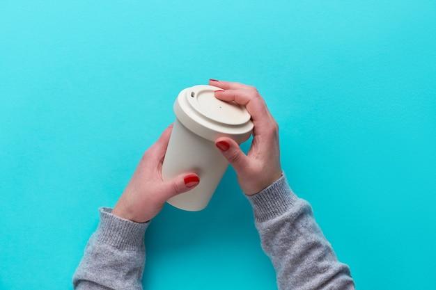 Mani in possesso di tazza di caffè riutilizzabile in bambù ecologico con coperchio in silicone. tazza da tè ecologica zero rifiuti su carta blu menta senza plastica. soluzione di viaggio per uno stile di vita sostenibile.